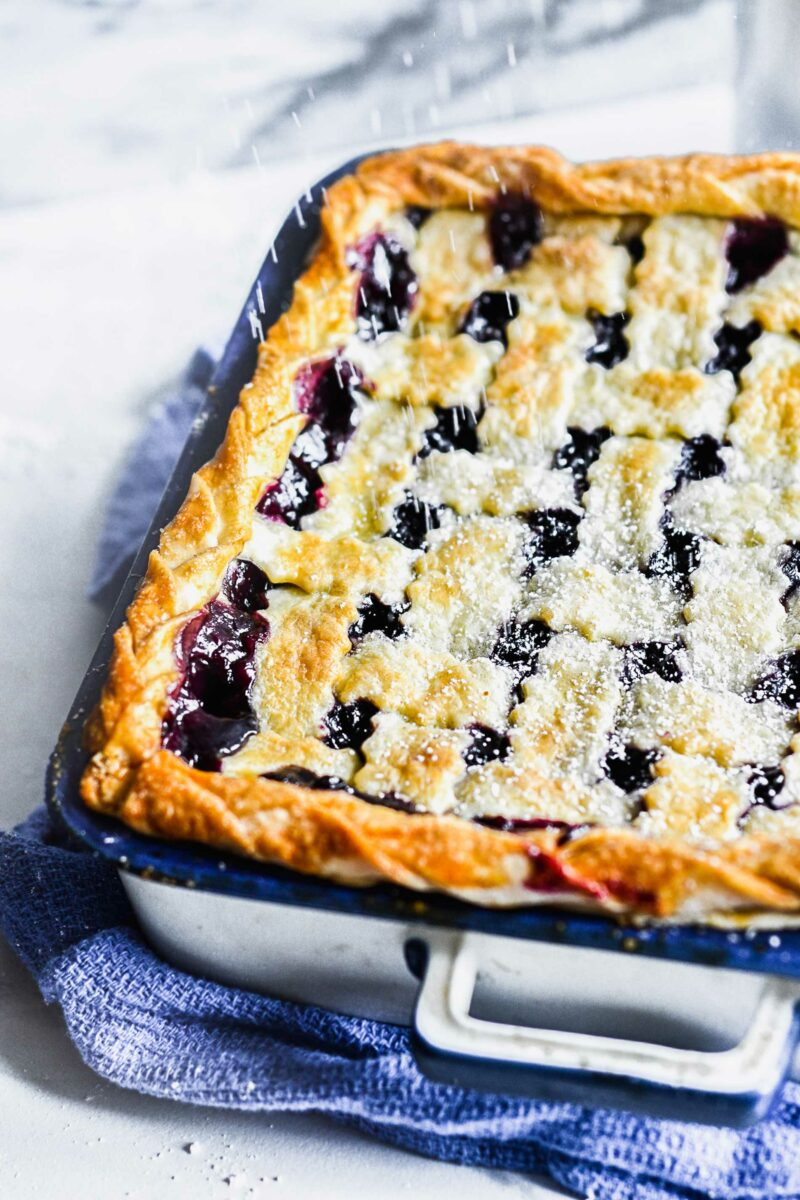 Powdered sugar is being sprinkled on top of a baked blueberry pie.