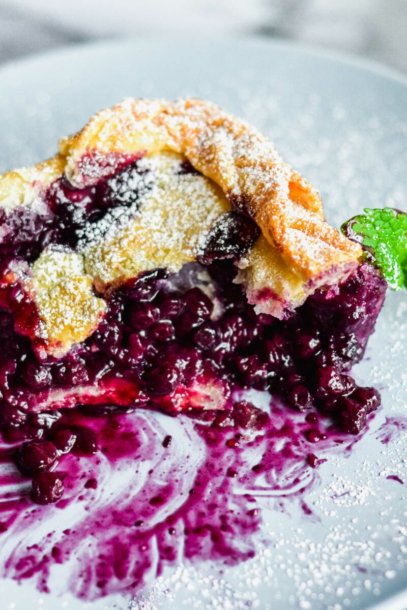 The baked blueberry pie has made a purple, juicy mess on a white plate.
