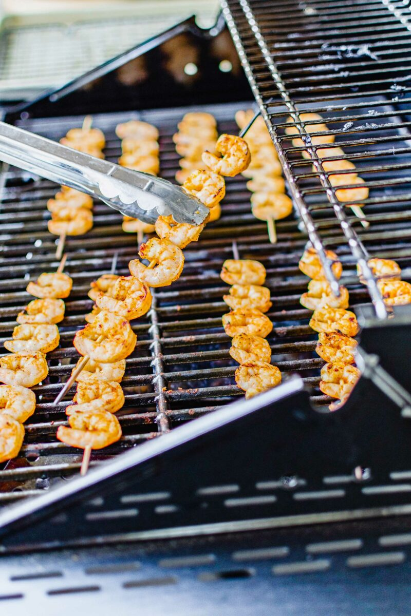 A shrimp skewer is being lifted from the grill.