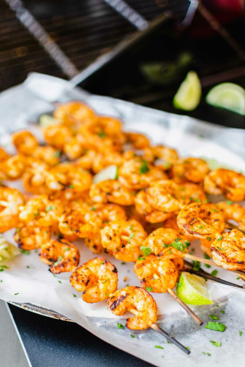 Grilled shrimp skewers are on a sheet of parchment paper.