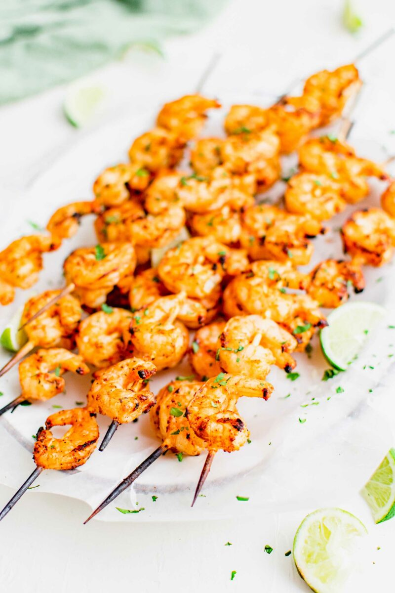 Shrimp skewers are garnished with cilantro and lime slices.