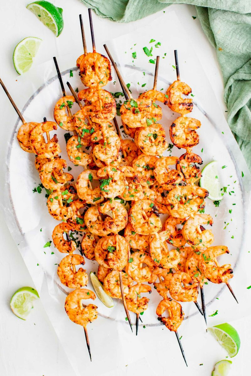 A white plate covered in parchment paper holds a large portion of shrimp skewers.