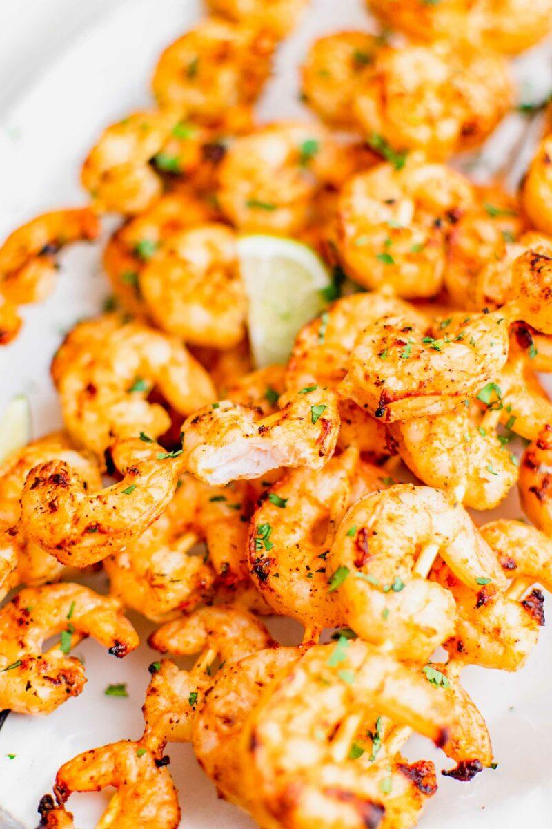 A bite of shrimp has been taken, revealing a cooked through white center.