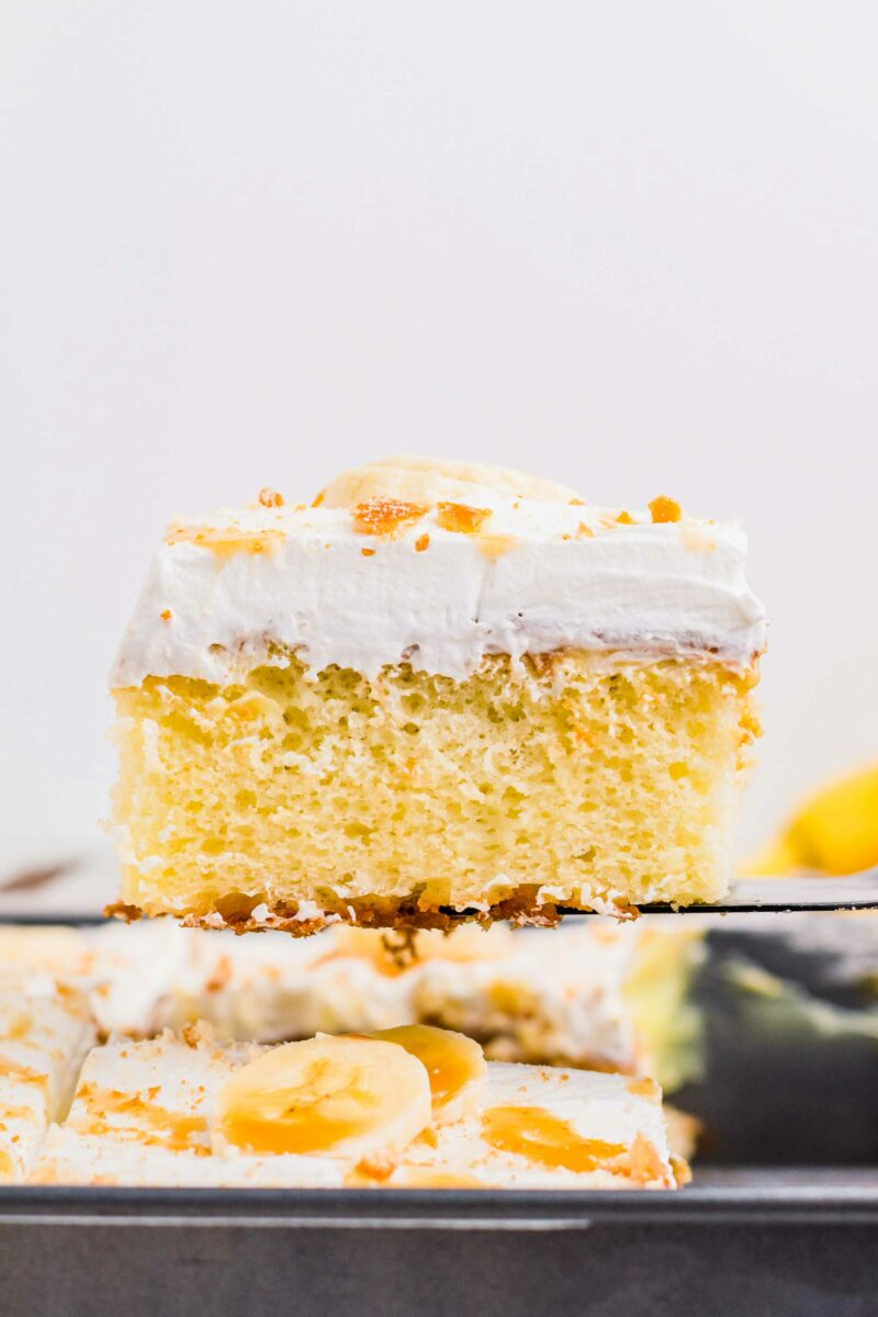 A square slice of cake is topped with whipped topping.