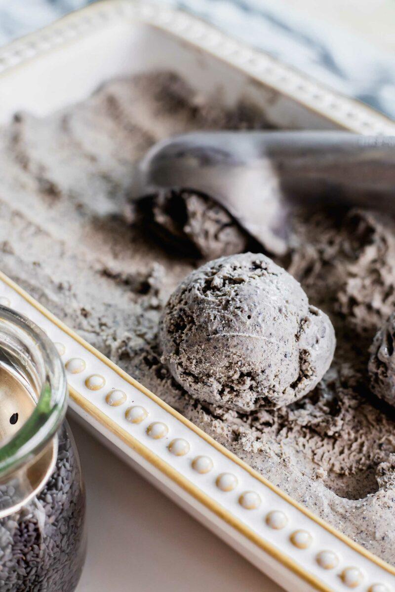 An ice cream scooper is scooping sesame ice cream.