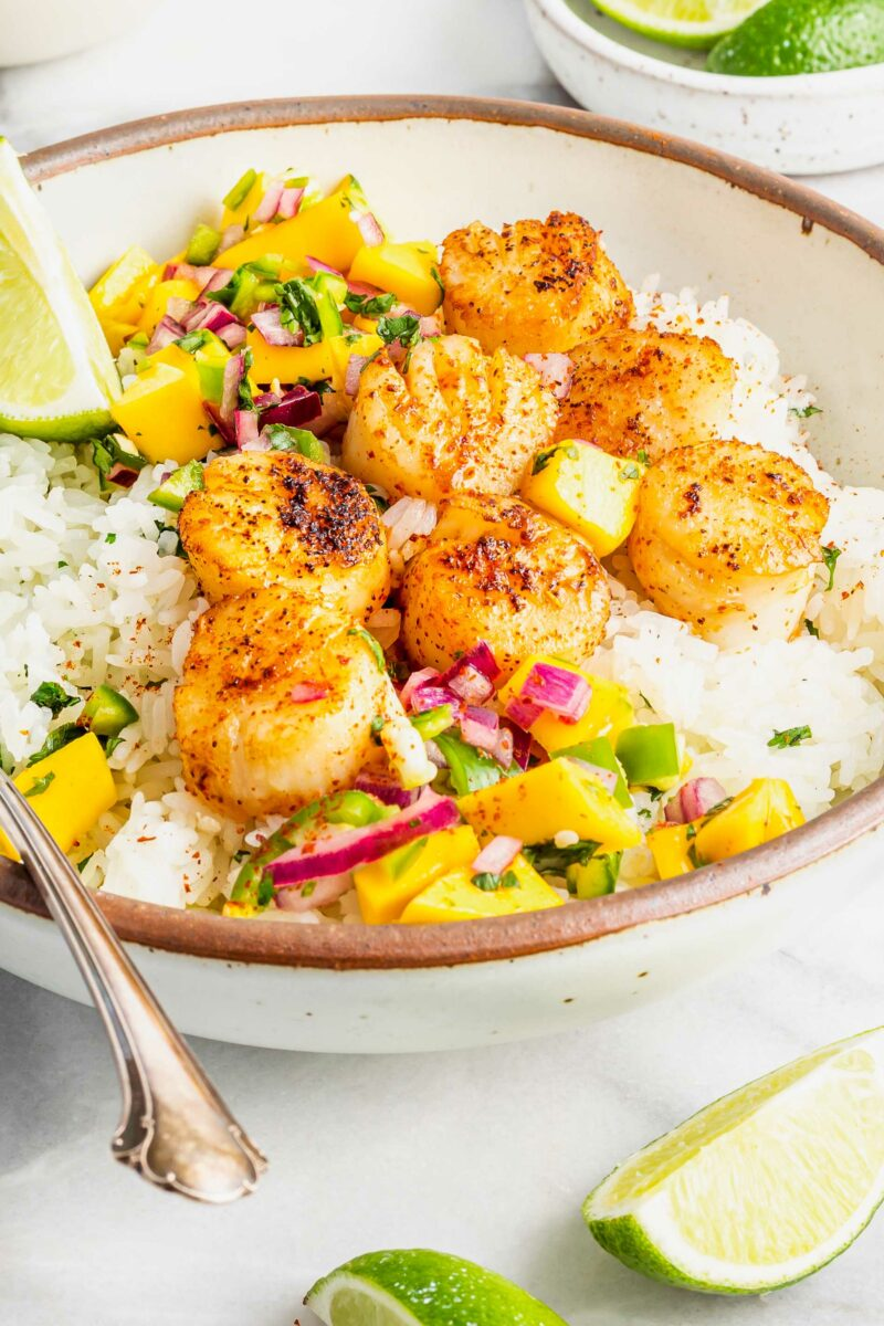 A tan and white bowl is filled with rice, relish, and scallops.