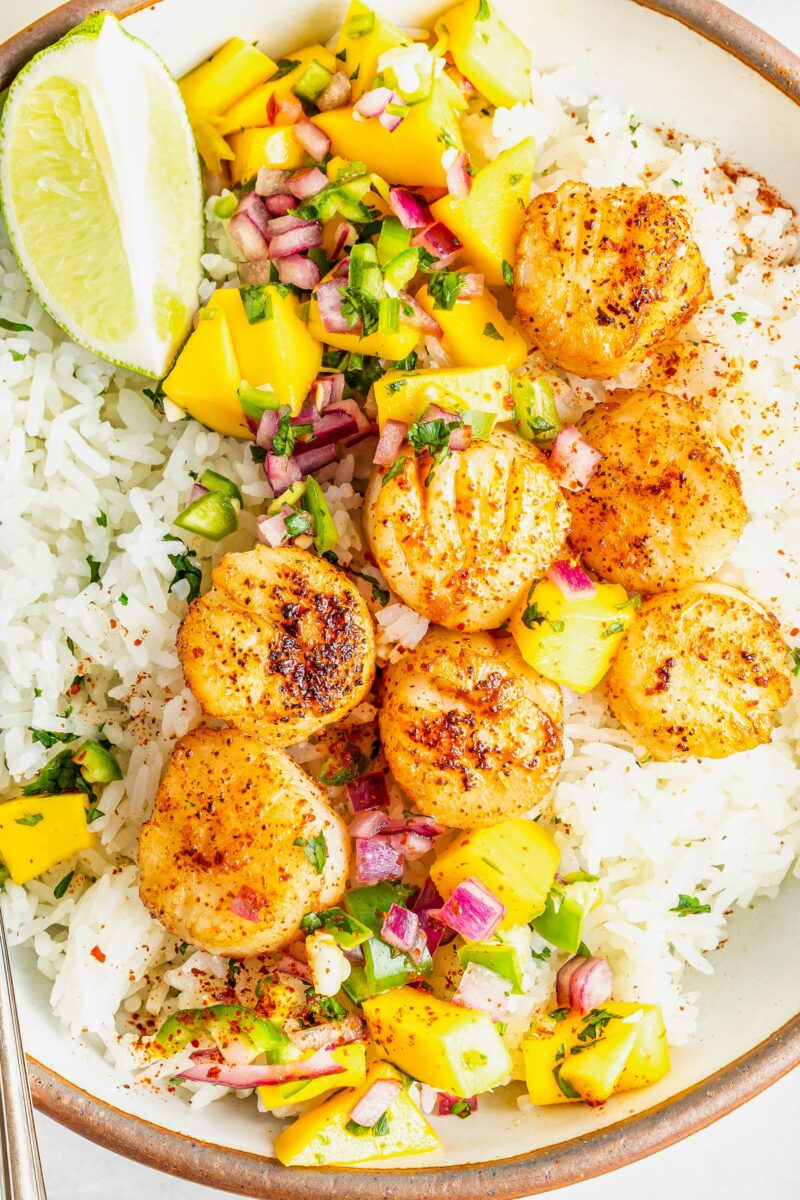 Cajun scallops are in a rice bowl with lime slices and mango relish.