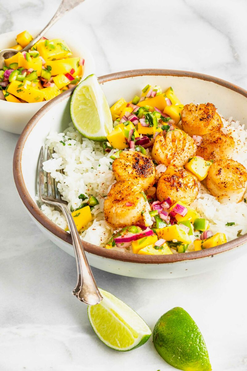 Lime wedges are placed on the outside of a rice and scallop bowl.