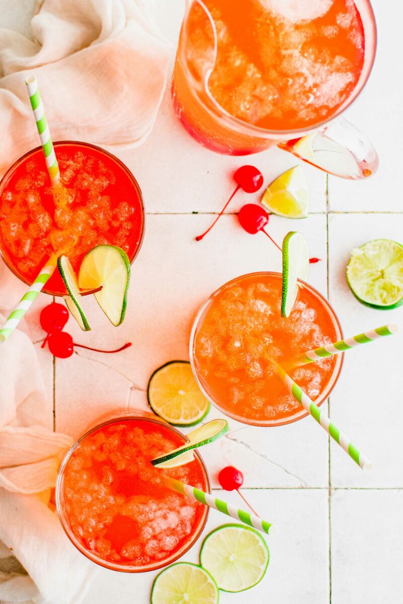 Four cherry limeades are placed on a white surface.