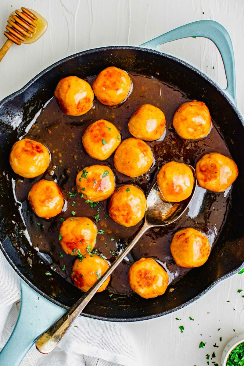 A black skillet is filled with chicken meatballs and hot honey sauce.