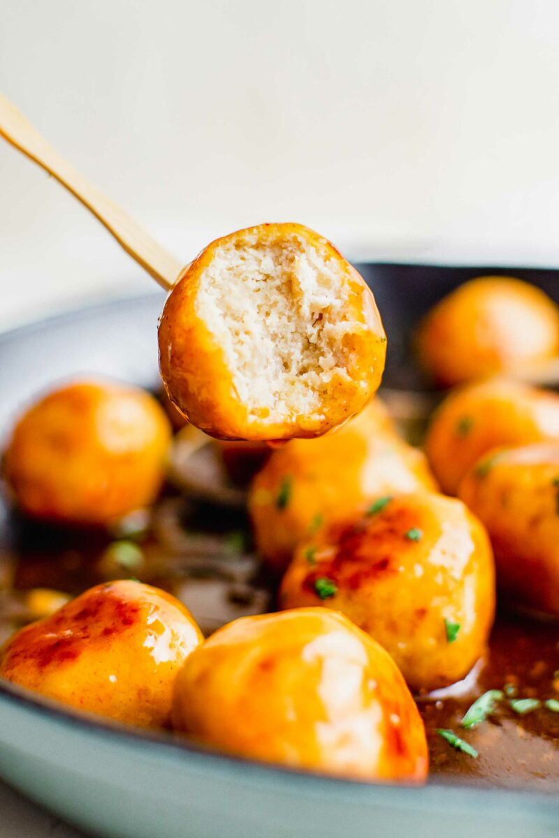 A skewer is lifting a bitten into meatball from the pan.