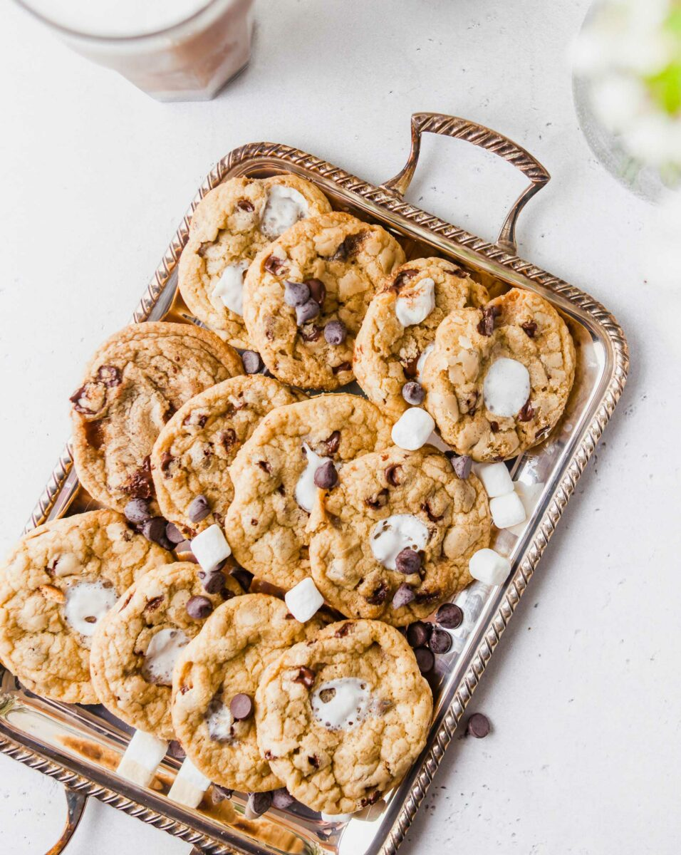 Marshmallows and chocolate chips are spread out over a tray of cookies.