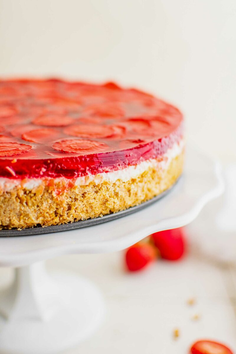 A strawberry pretzel salad is uncut and presented on a white cake stand.