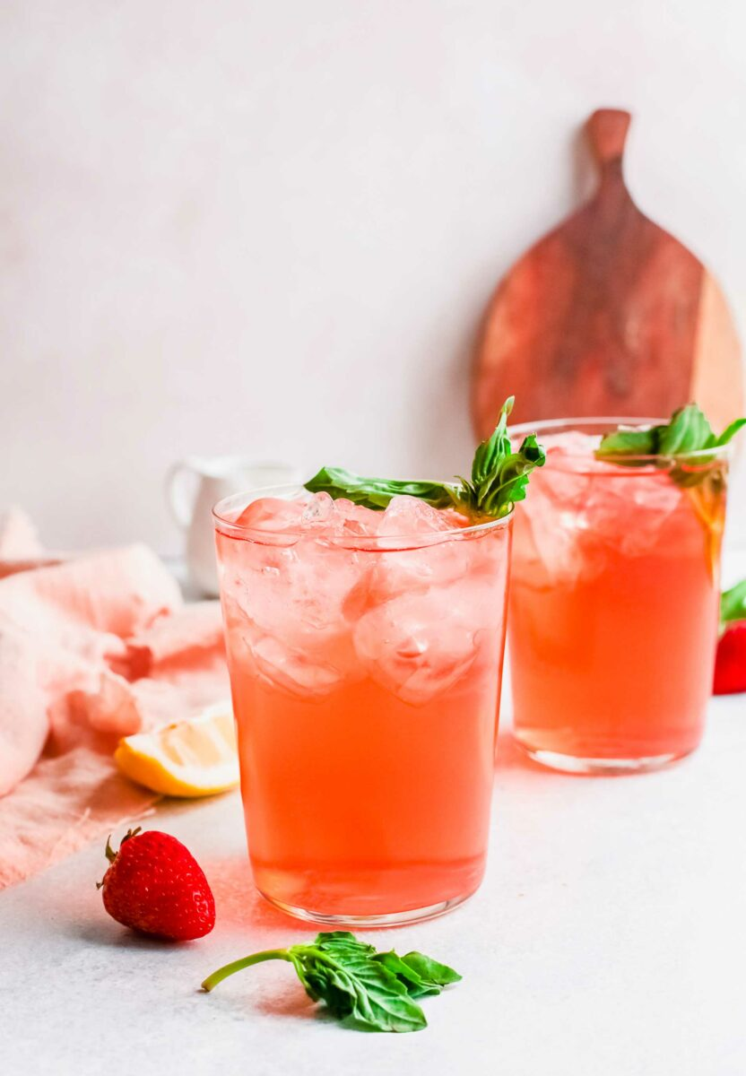 Two glasses of strawberry rickeys are placed on a white countertop.