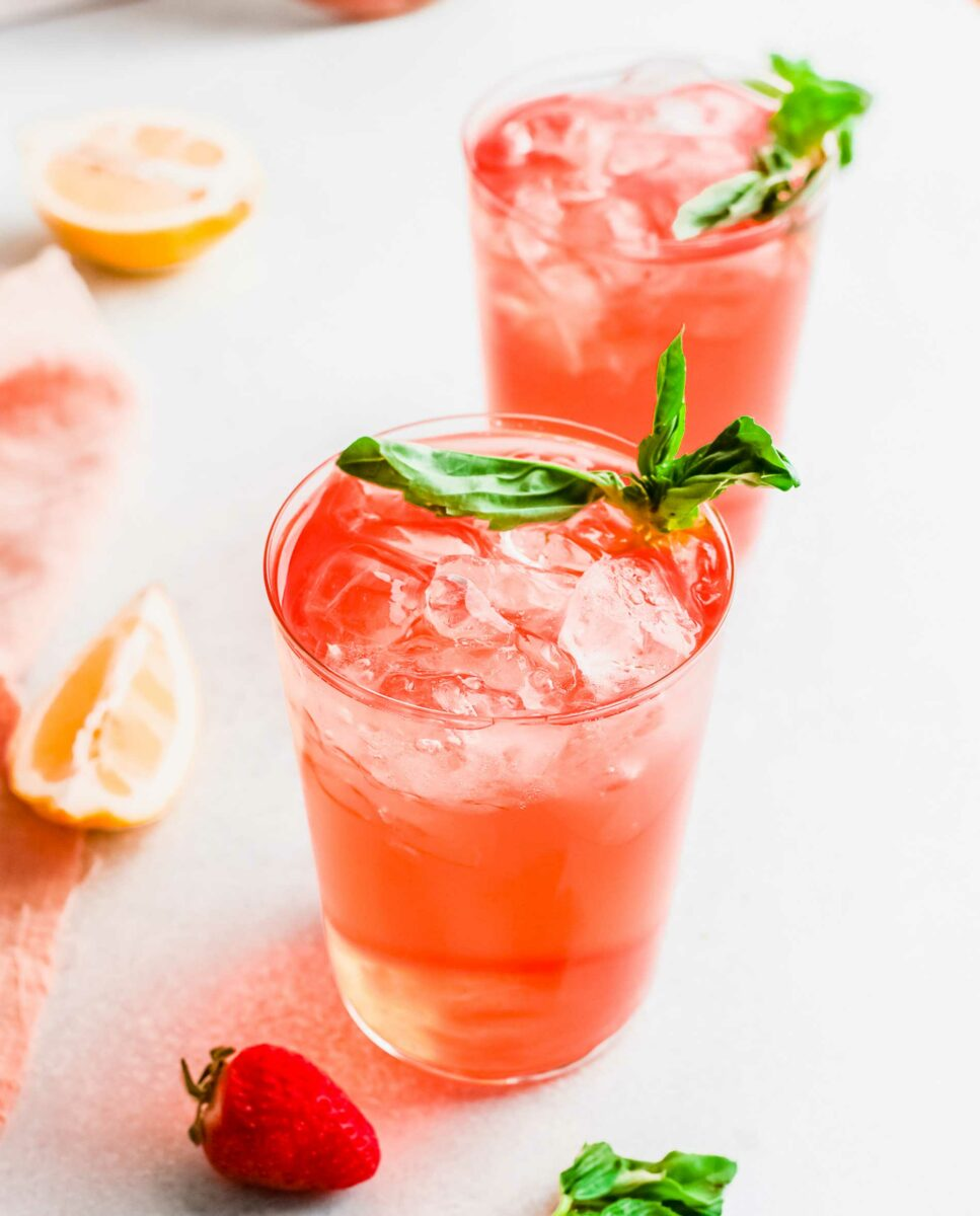 Two strawberry gin rickeys are placed on a white counter top and garnished with basil.