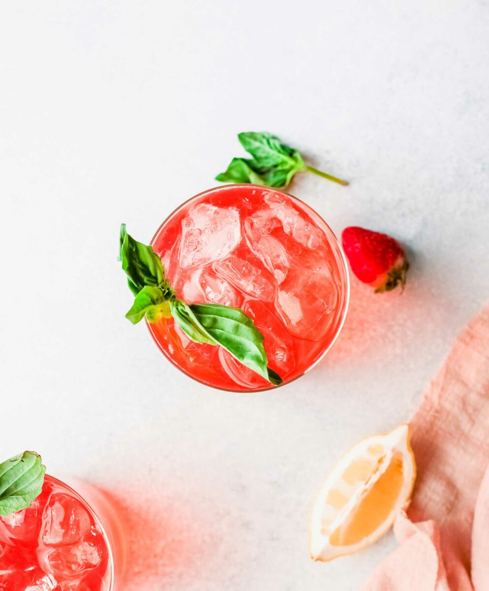 Ice and basil are floating at the top of a vibrantly pink rickey.