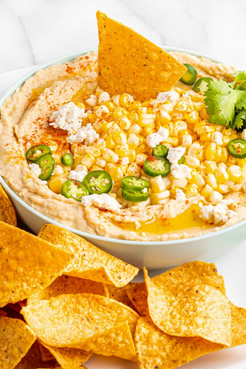 A tortilla chip is being dipped into street corn hummus.