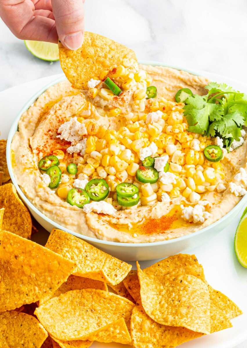 A chip has been dipped into street corn hummus.