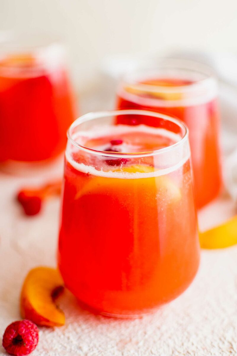 Several glasses of summer punch are on a white surface.