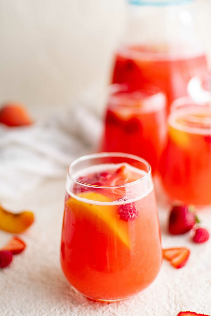 A cup of punch has fruit floating around in it.