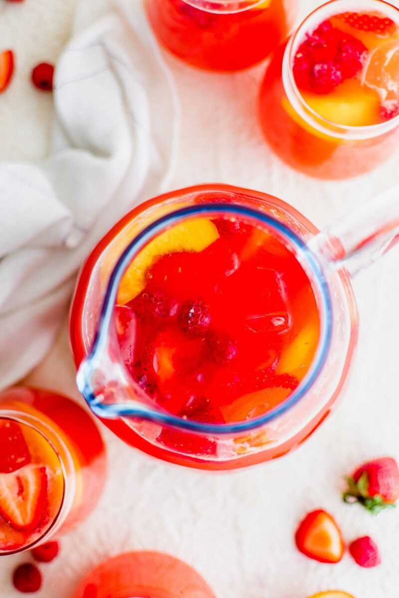 A pitcher of summer punch is placed on a white surface.