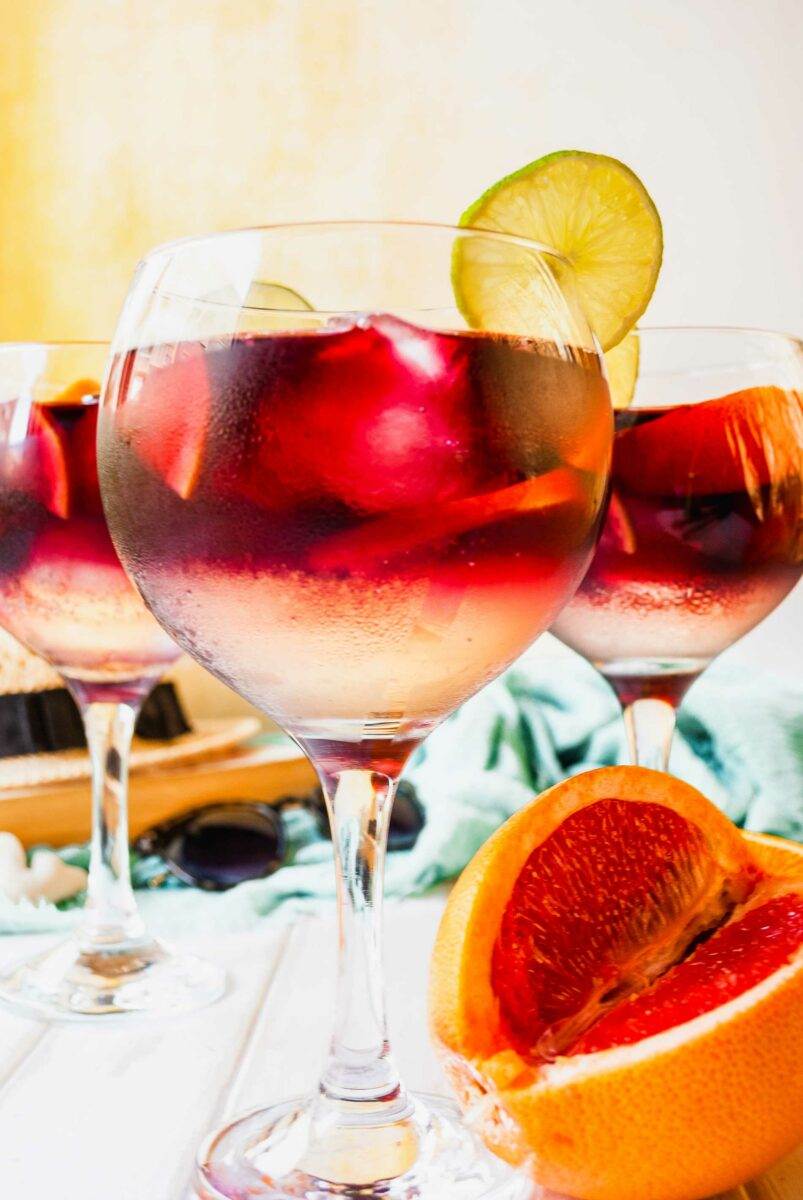 Three glasses of Tinto de Verano are placed on a white surface.