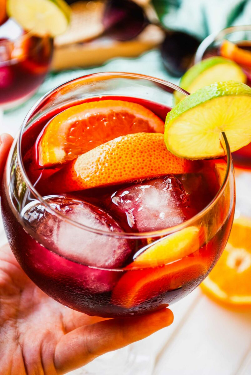 A small round glass is filled with ice cubes, wine, and fruit slices.
