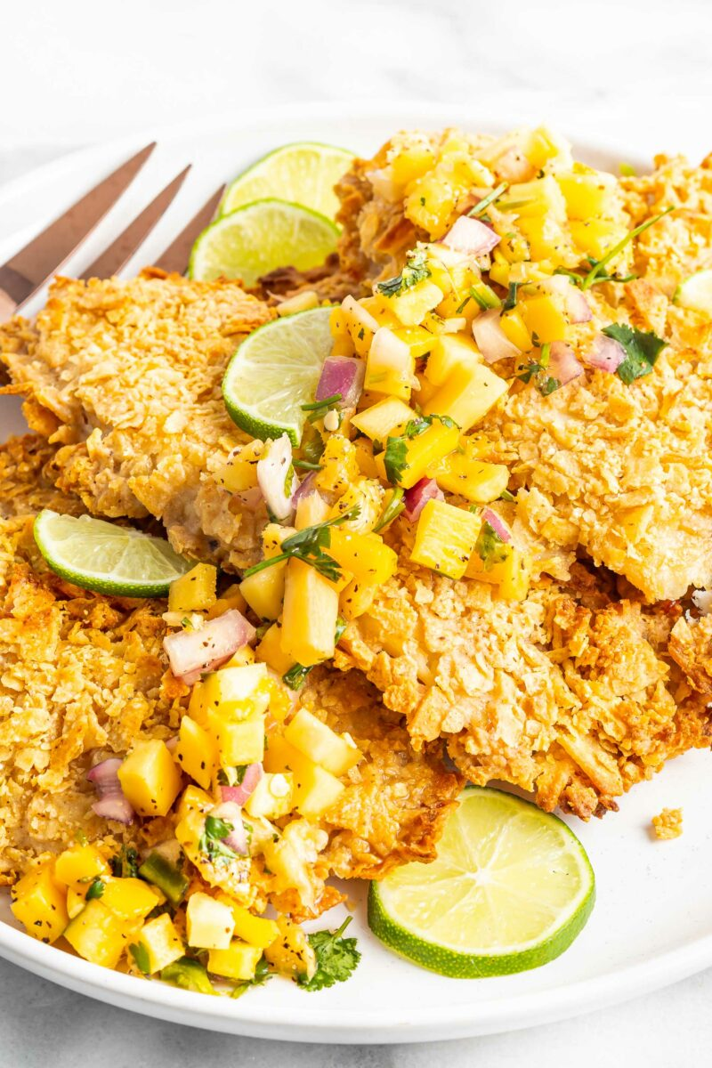 Baked tortilla crusted tilapia is garnished with limes and mango.