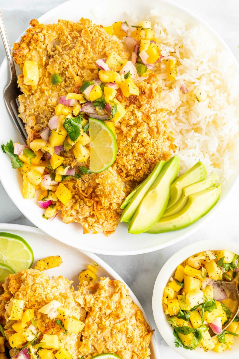 Mango salsa is in a small bowl next to a plate of rice and tortilla crusted tilapia.