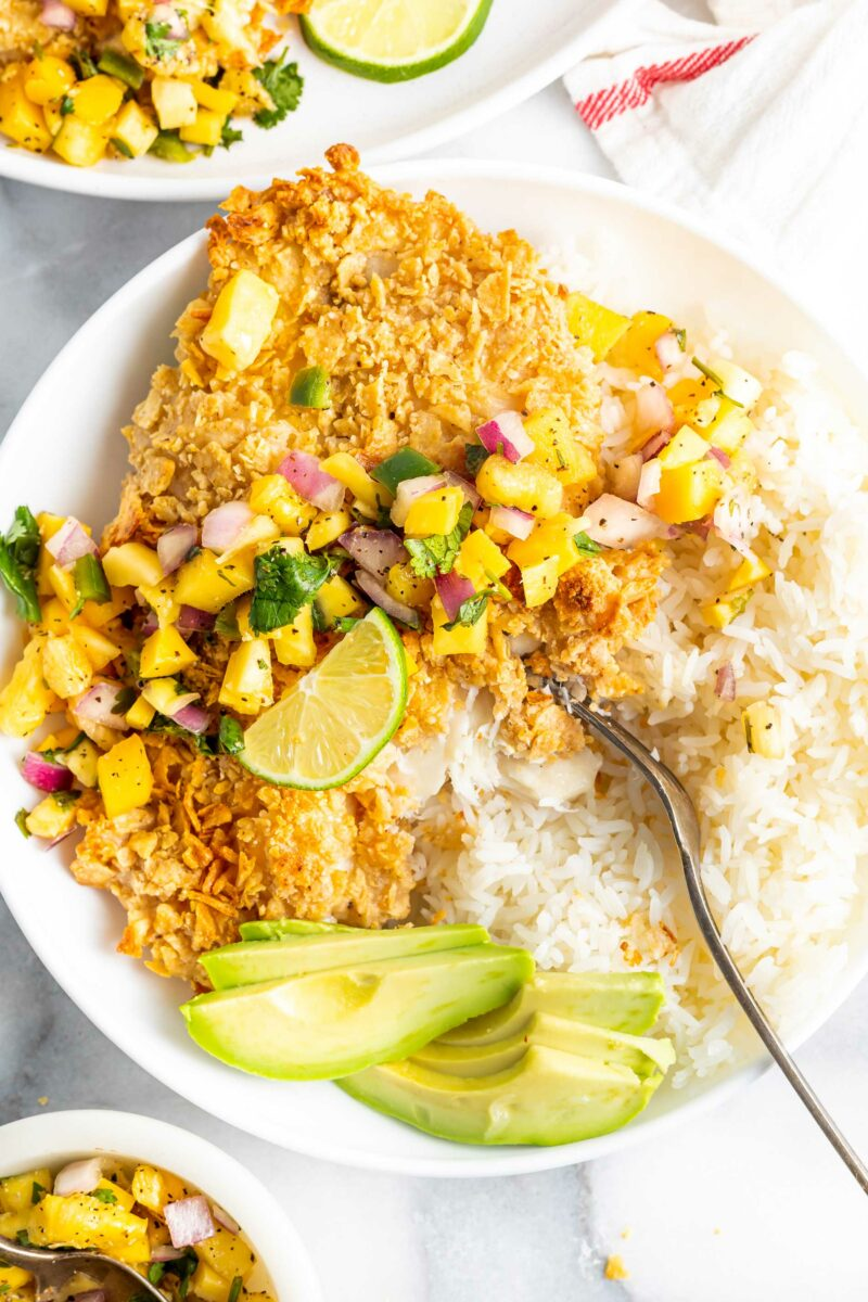 White rice, sliced avocado, limes and mango slaw are plated with baked fish.