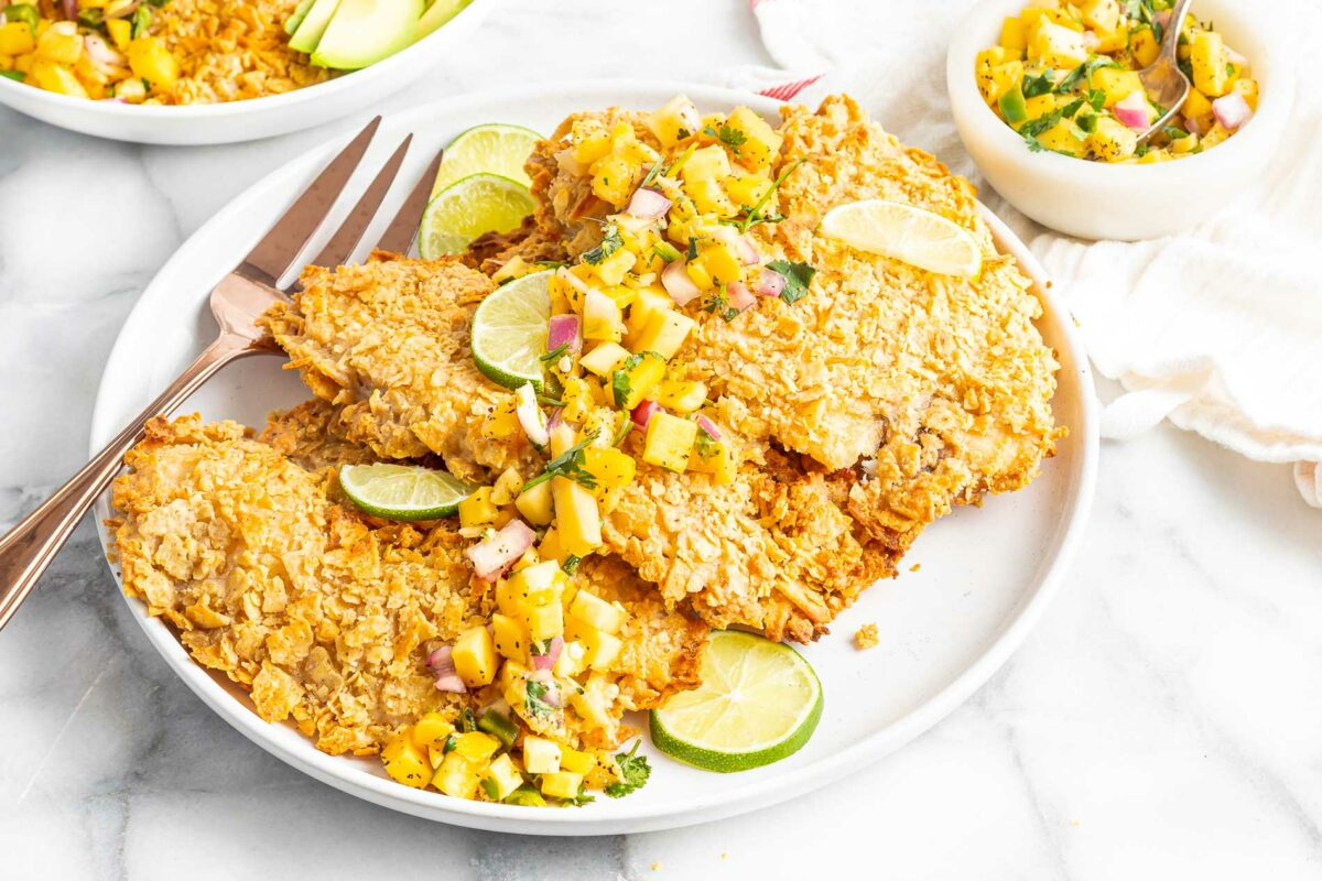 A fork is set on a white plate with several crusted tilapia filets.