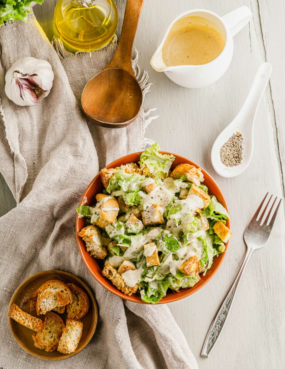 A fork is placed next to a bowl filled with Caesar salad.