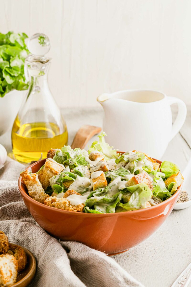 Olive oil is placed in a large glass jar behind a bowl of Caesar salad.