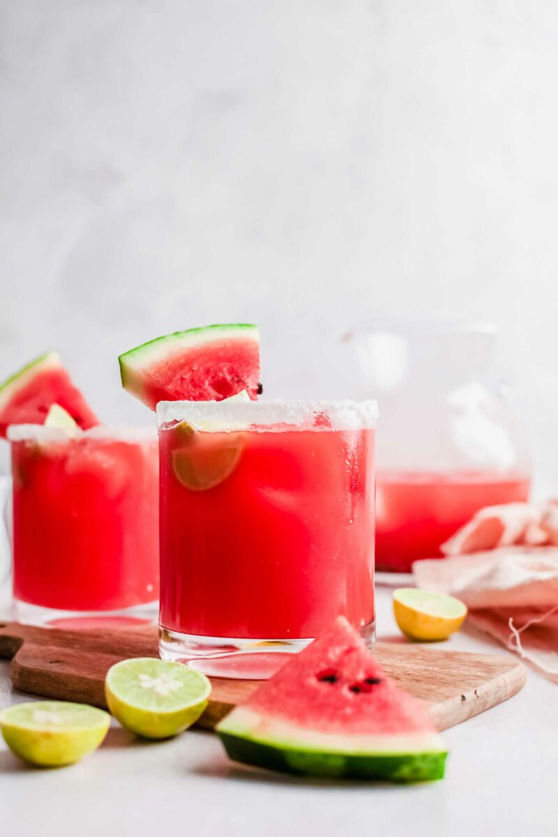 Vibrant pink watermelon Palomas are placed on a wooden surface.