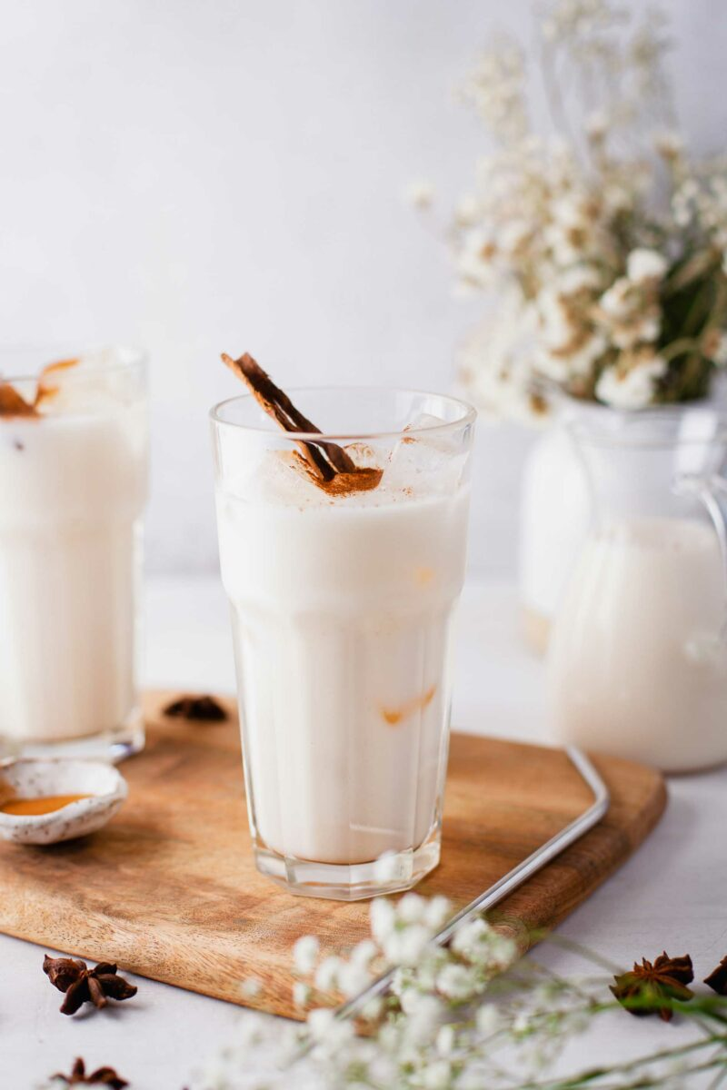 Two glasses of horchata are placed on a wooden board.