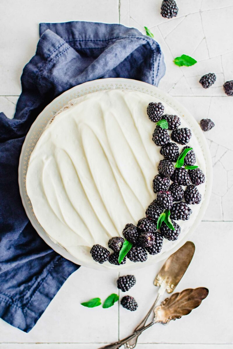 A frosted blackberry cake is garnished with blackberries.