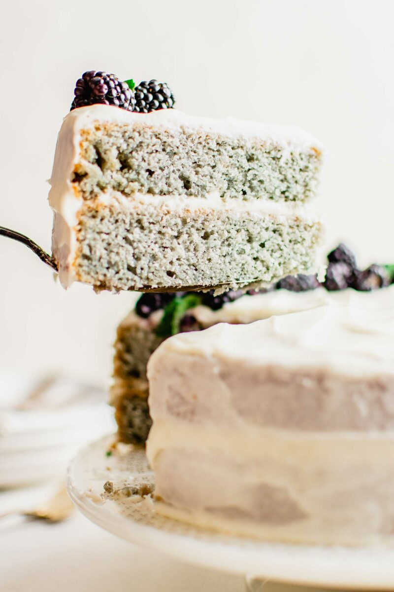 A slice of blackberry cake is being removed from the rest of the cake.
