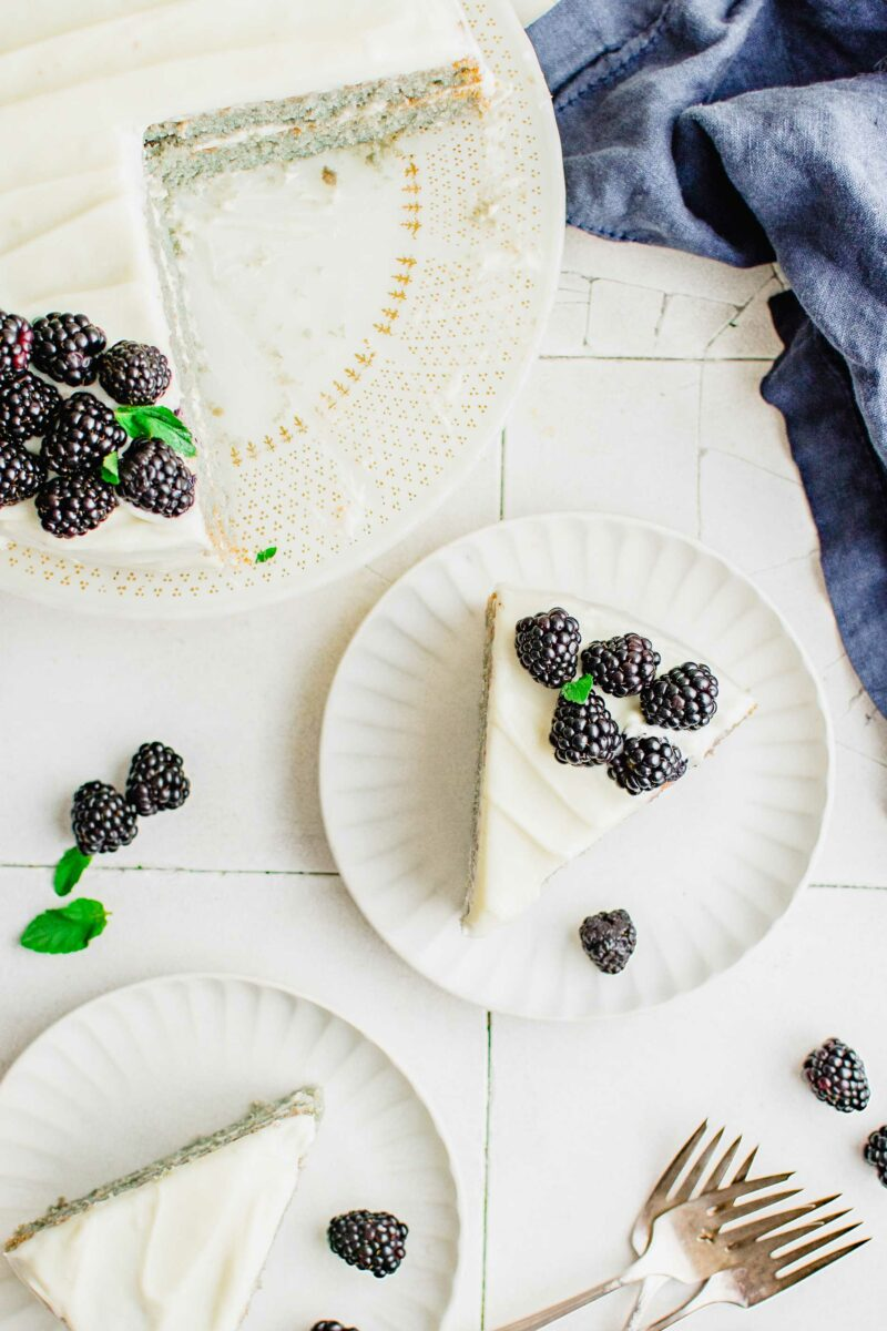 Blackberries garnish a slice of cake that's on a white plate.