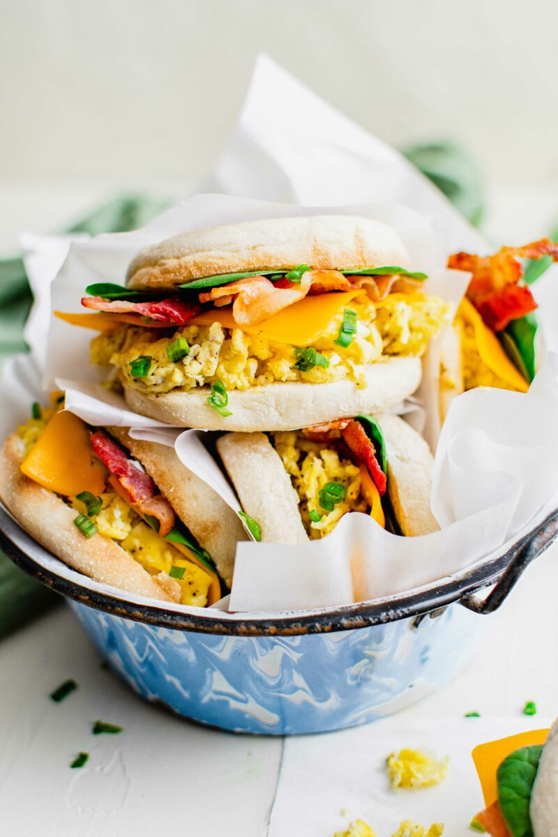 Several sandwiches are placed with parchment paper in a bowl.