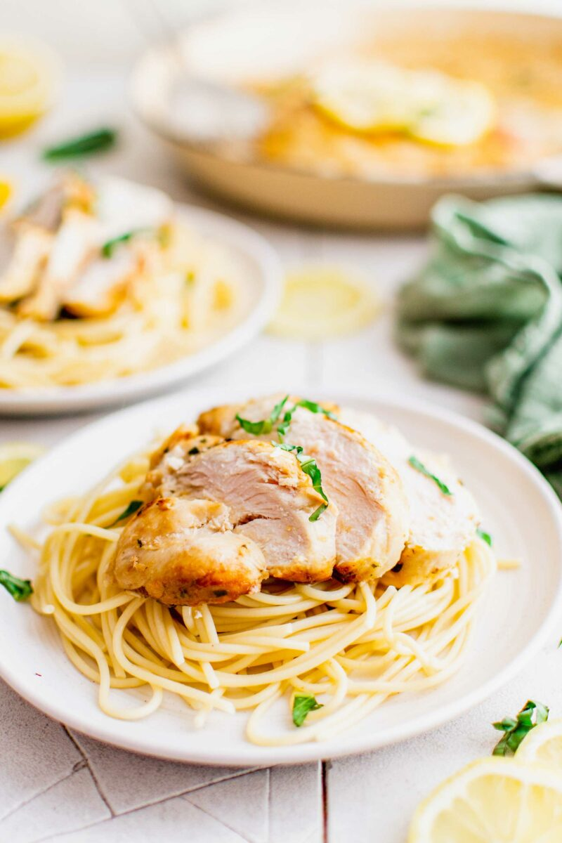 A sliced chicken breast is served over a portion of spaghetti noodles on a white plate.