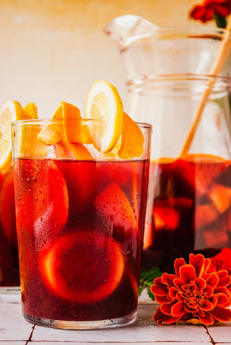Orange flowers are placed on a tile surface next to a glass of sangria.