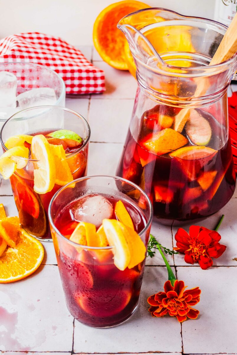 Two glasses of sangria are placed next to a half full pitcher.
