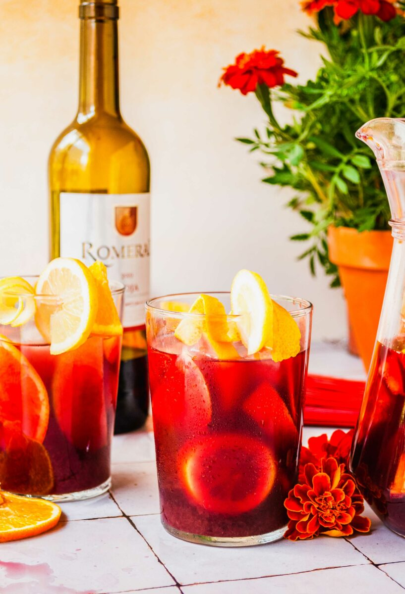 Several glasses are filled with vibrant red sangria and slices of citrus.