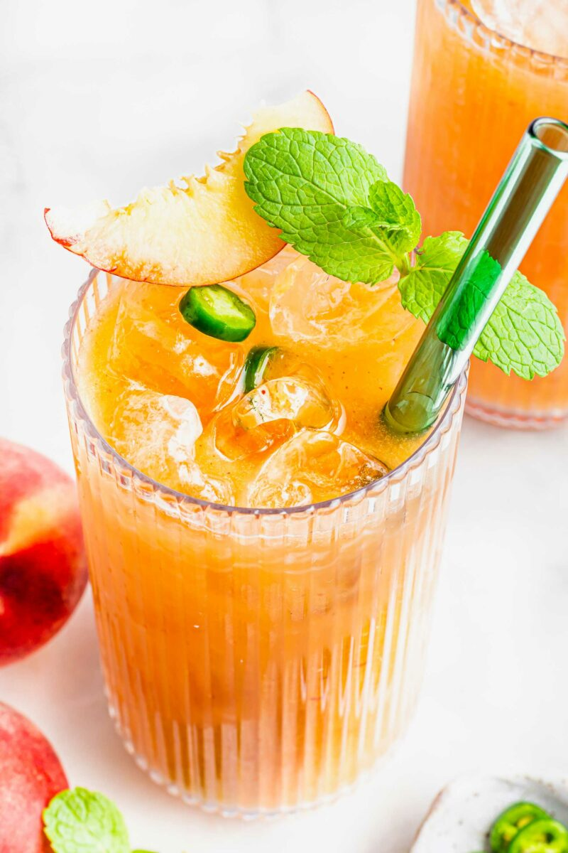 A straw is placed in a glass of spicy peach agua fresca.