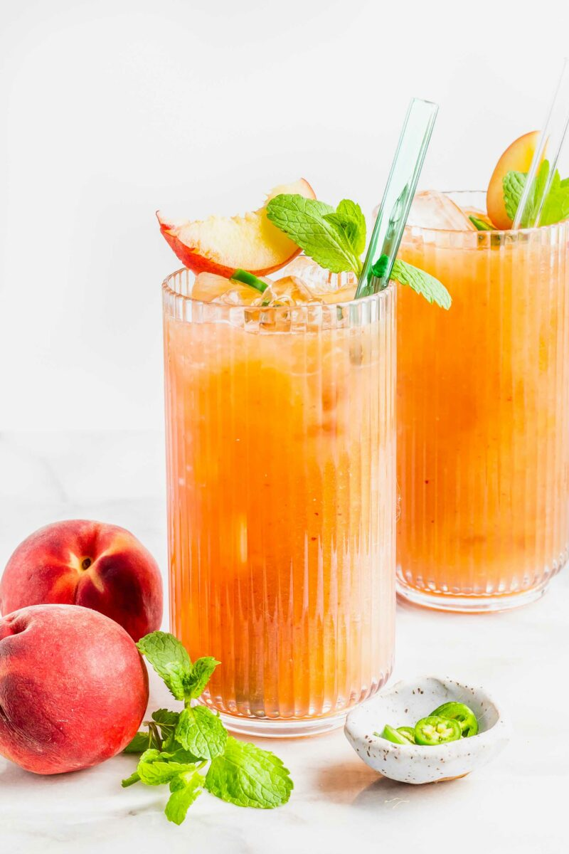 Two glasses are filled with spicy peach drinks.