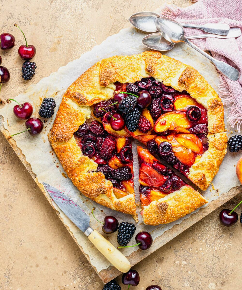 A slice of fruity galette has been cut from the rest of the dessert.
