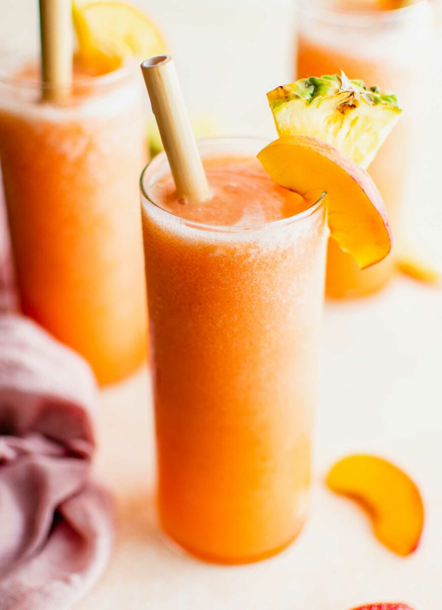 A glass filled with orange slushy is topped with fresh fruit.