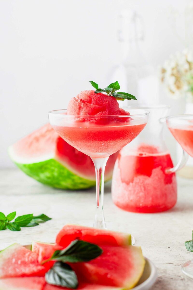 A glass of frosé is garnished with a mint sprig.