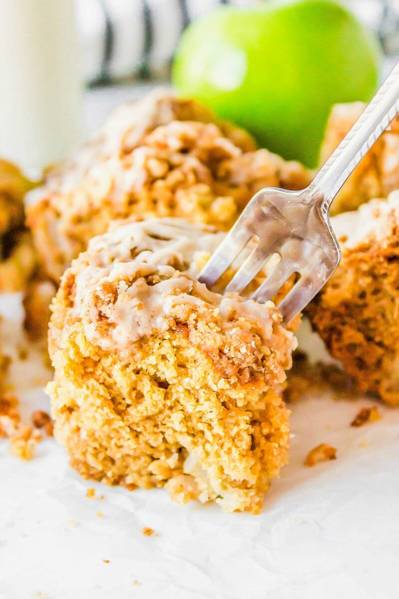 A fork is plunging into a piece of coffee cake.