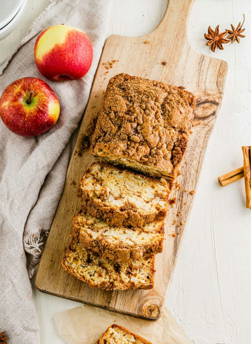 A loaf of apple cinnamon swirl bread is being sliced on a wooden cutting board.